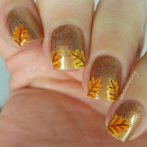 Here is another design for short nails that is super cute for Autumn. Paint  your nails with gold glitter polish and then paint pretty leaves in orange  and ... - Fall Nail Designs 2018: 40 Cute Fall Nail Art Ideas LadyLife