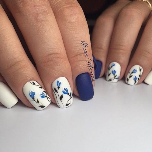 This look is really cute with its fun floral design on two fingernails.  Paint two nails dark-blue and three fingers white. Use blue and dark-blue  to paint a ... - Nail Designs For Short Nails 2018: 25 Cute Short Nail Designs Ideas